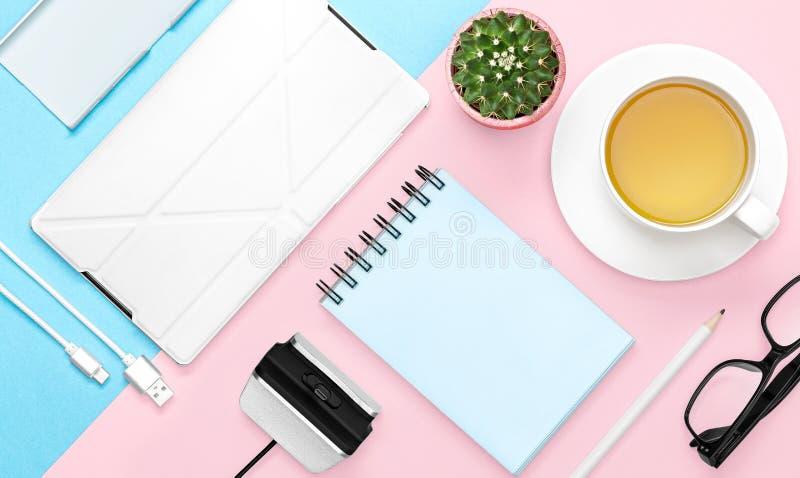 办公桌平的位置照片有盒的电话和片剂、笔记本、茶杯子、铅笔,仙人掌,桃红色和蓝色背景的 免版税库存图片