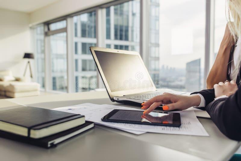 办公桌特写镜头视图:膝上型计算机,笔记本,纸,在现代顶楼房屋的片剂计算机 免版税库存照片