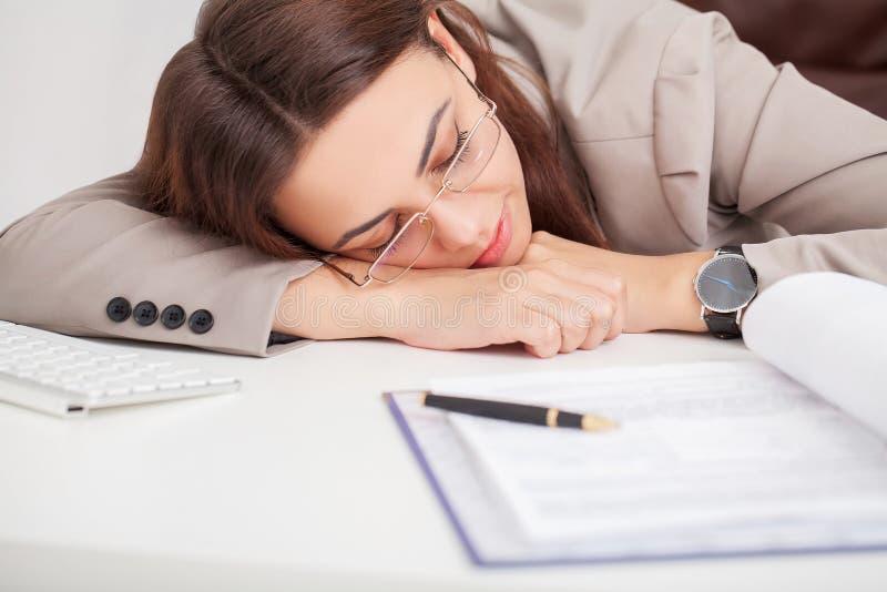 办公桌的年轻疲乏的妇女睡觉与眼睛的关闭了, slee 免版税库存照片