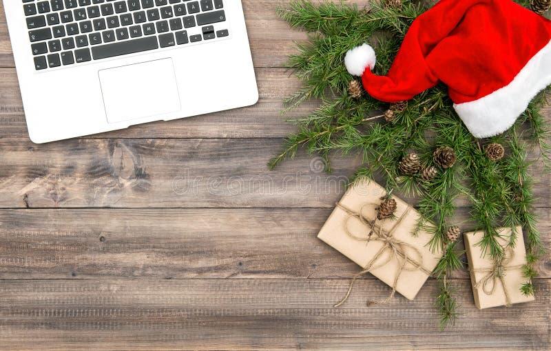办公桌膝上型计算机圣诞节装饰红色帽子礼物 库存照片