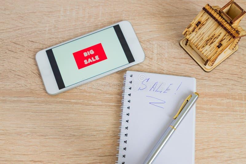 办公桌顶视图有白色智能手机的有销售文本、笔记和小木房子的 技术企业网络购物和 免版税库存图片