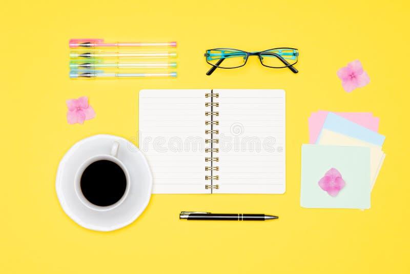 办公桌顶视图照片有空白嘲笑开放笔记薄、笔、玻璃和杯子的在淡色背景舱内甲板位置的咖啡 免版税库存照片