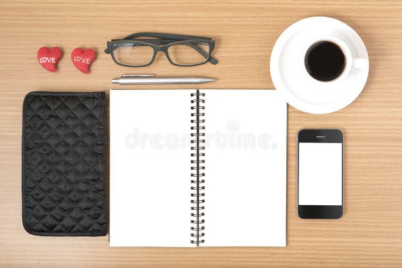 办公桌:与电话,笔记薄,镜片,钱包,心脏的咖啡 库存照片