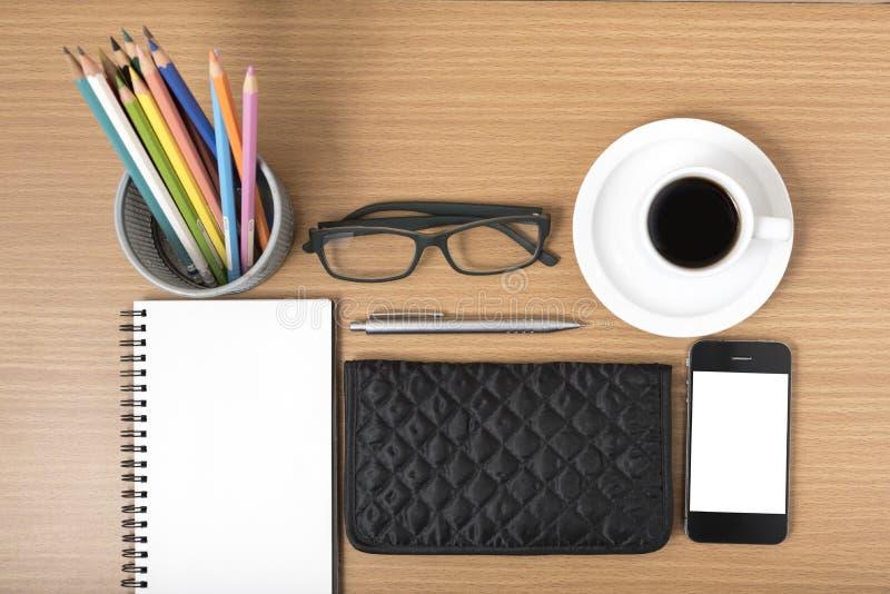 办公桌:与电话,笔记薄,镜片,钱包,颜色的咖啡 库存图片
