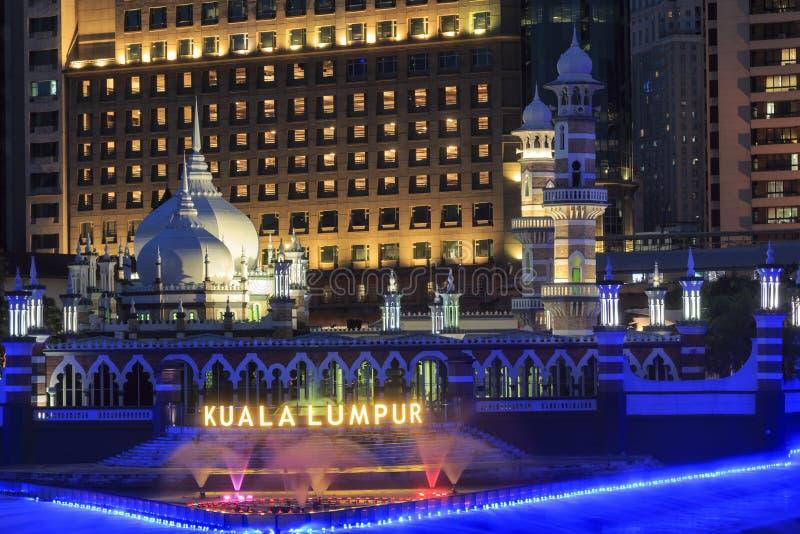 办公楼和苏丹阿卜杜勒萨玛德Jamek清真寺有喷泉的在晚上点燃了在巴生和Gombak河的河岸 免版税库存照片