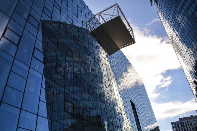 办公楼现代建筑学  从玻璃和金属的一个摩天大楼 反射在天空蔚蓝窗口里  商业中心 免版税图库摄影