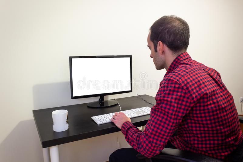 办公计算机的人在木黑书桌大模型 被加点的红色衬衣,LCD屏幕,键盘,老鼠,台式电脑,办公室椅子 库存图片