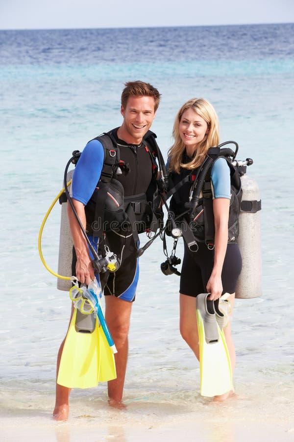 加上享受海滩假日的佩戴水肺的潜水设备 免版税图库摄影