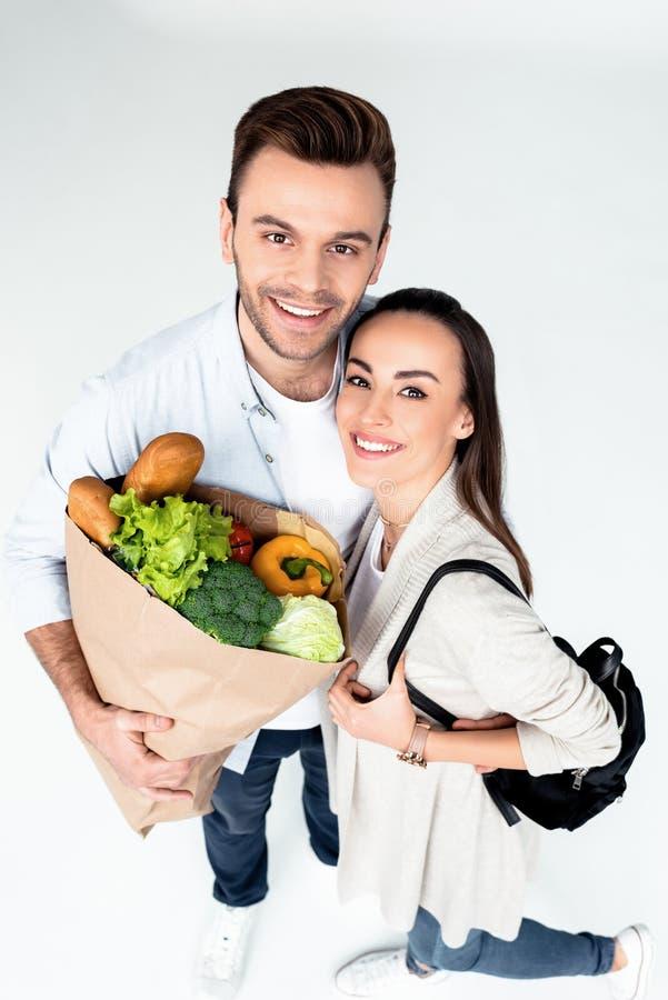 年轻加上微笑对照相机的食品杂货袋 免版税库存图片
