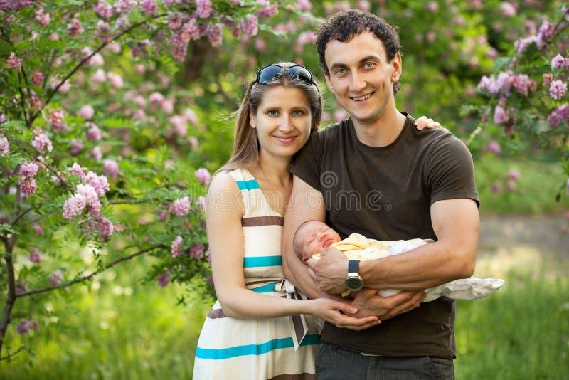年轻加上户外新出生的儿子在春天 免版税图库摄影