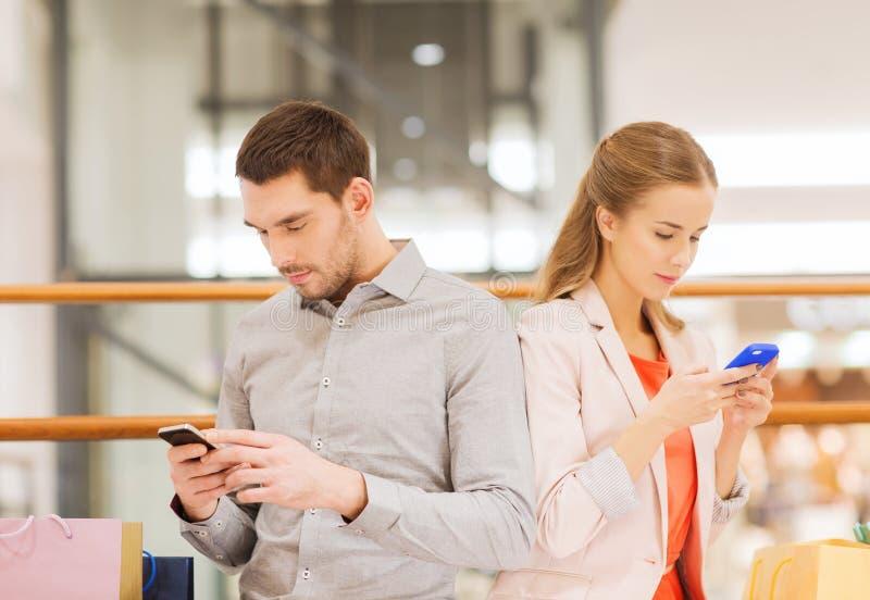 加上智能手机和在购物中心的购物袋 免版税库存照片