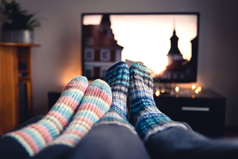 加上袜子和羊毛长袜电影或者系列在电视在冬天 一起或说谎坐沙发的妇女和人 库存照片