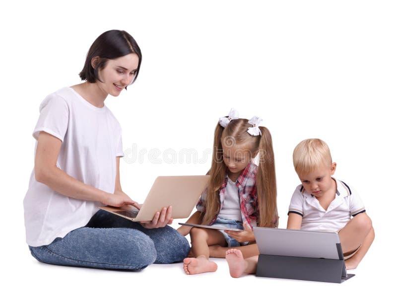 加入她的孩子的一名美丽的妇女对现代技术隔绝在白色背景 免版税图库摄影