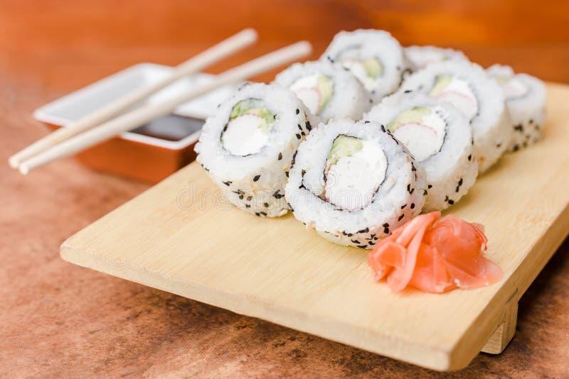加利福尼亚寿司卷用在一张木桌上的酱油 图库摄影