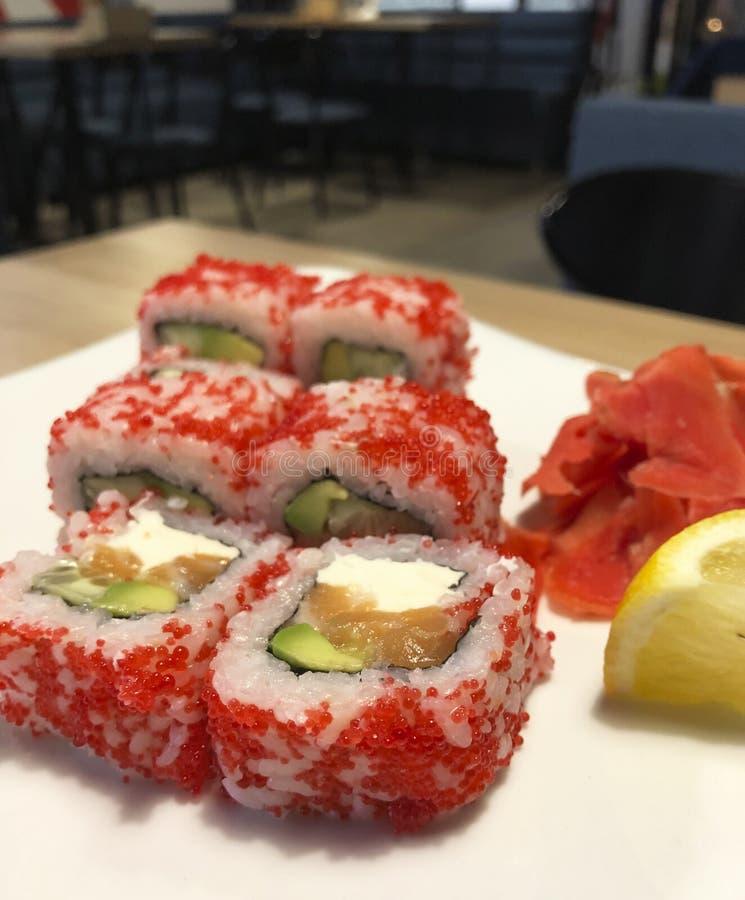 加利福尼亚美丽的寿司用在一块板材的红色鱼子酱在咖啡馆用柠檬 免版税图库摄影