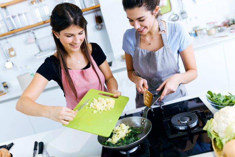 加土豆的两个美丽的少妇到唐莴苣入平底锅 免版税库存照片
