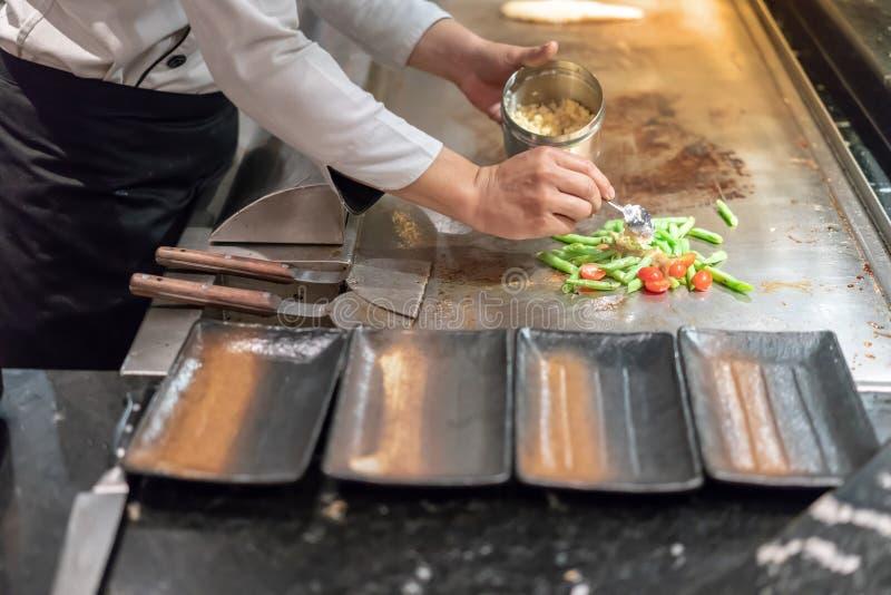 加在沙拉的厨师的手大蒜在顾客前面 免版税库存图片