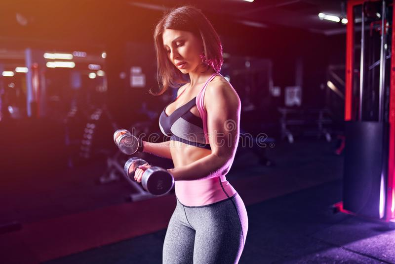 加大与哑铃的残酷运动妇女muscules 免版税库存照片