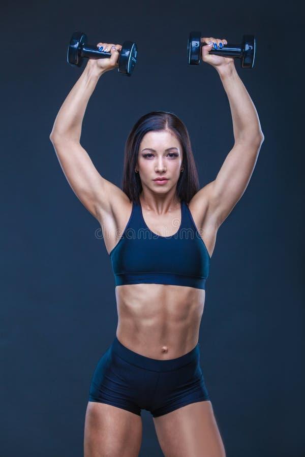 加大与哑铃的残酷运动性感的妇女muscules 锻炼的概念炫耀,给健身房做广告 库存图片