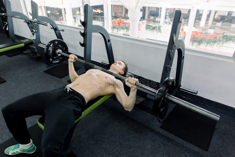 加大在长凳的年轻运动人肌肉压入健身房 在健身房的年轻爱好健美者训练:胸口-杠铃 图库摄影