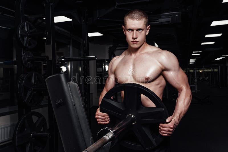 加大干涉和训练在健身房的肌肉坚强的运动人 做与杠铃的英俊的爱好健美者人锻炼 免版税库存图片