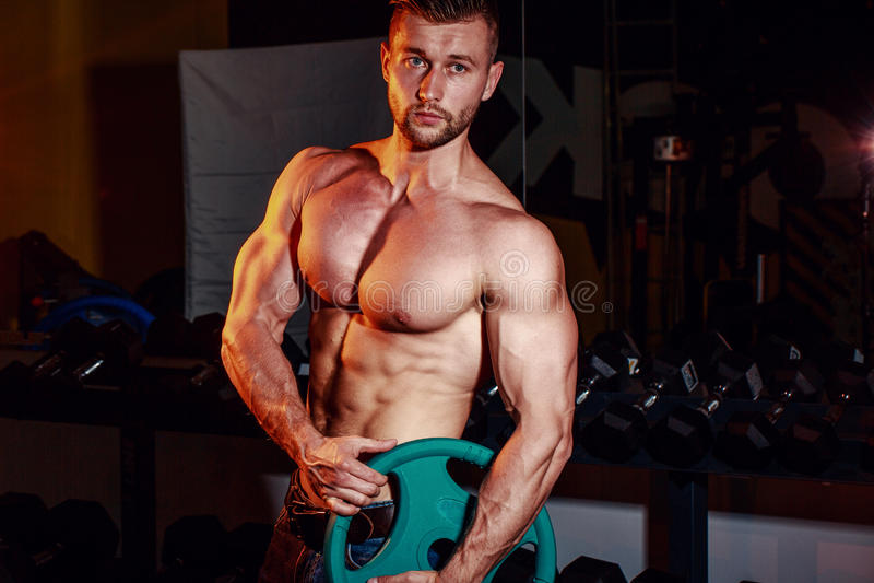 加大干涉和训练在健身房的肌肉坚强的运动人 做与杠铃的英俊的爱好健美者人锻炼 库存图片