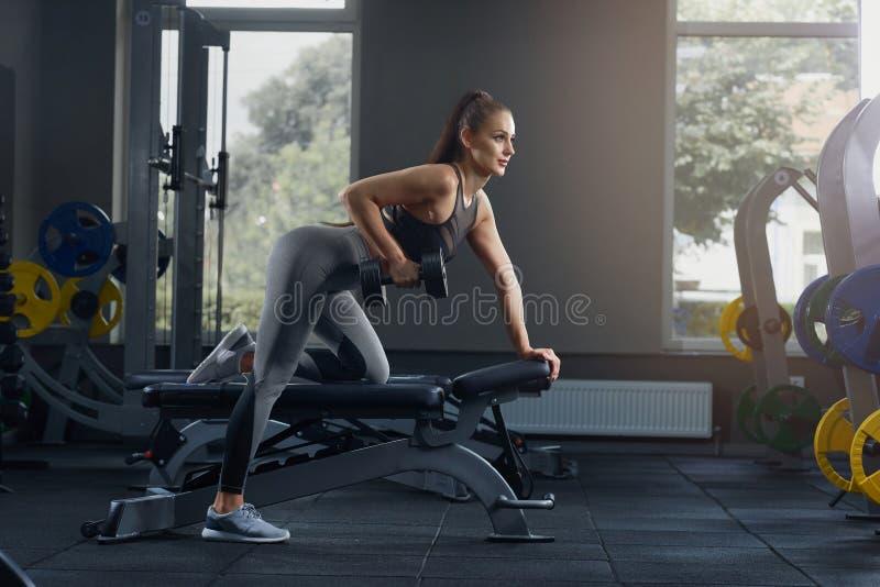 加大性感的运动的妇女干涉与哑铃在健身房 免版税库存图片