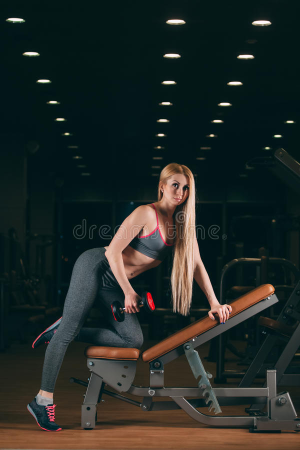 加大残酷运动的妇女干涉与在健身房的哑铃 免版税库存照片
