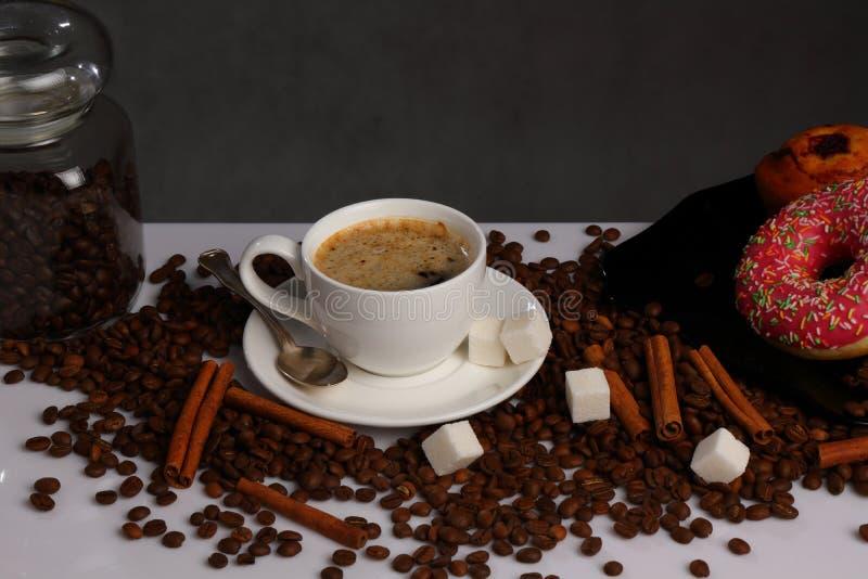 加奶咖啡杯、咖啡豆、桂香和油炸圈饼 免版税库存图片