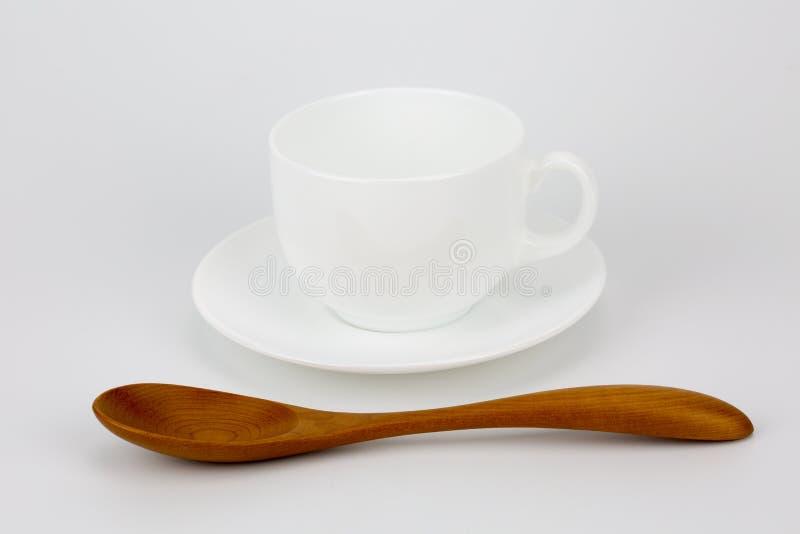 加奶咖啡杯子和棕色木匙子 库存照片