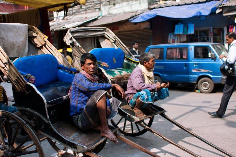 加尔各答,印度:手被拉扯的人力车的年长工作者坐室外并且等待乘客 库存照片