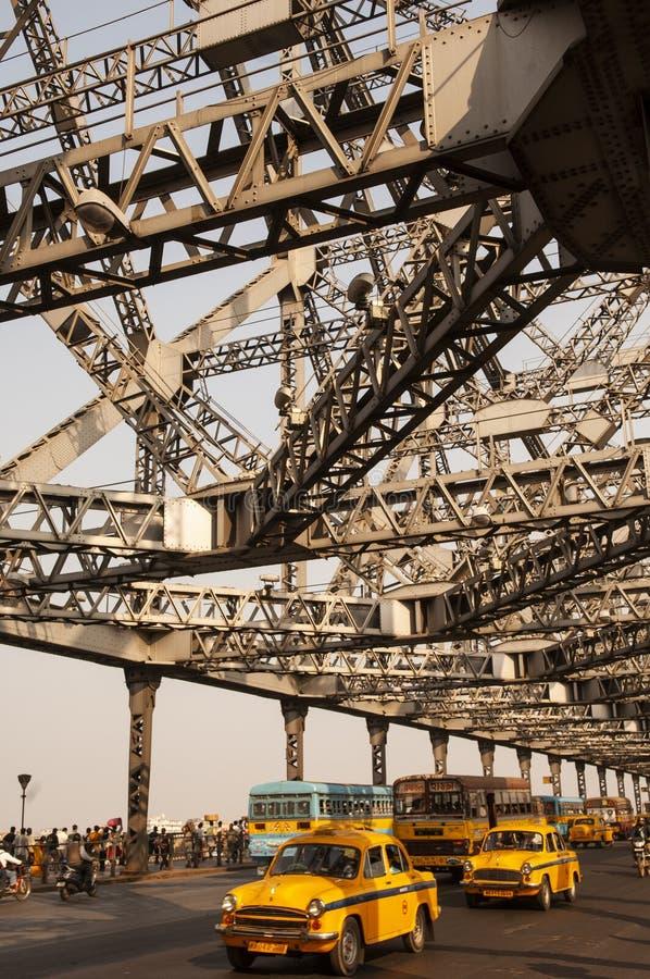 加尔各答/印度 — 2012年2月2日:公共交通通过历史悠久的豪拉桥,穿过呼啸的河 库存图片
