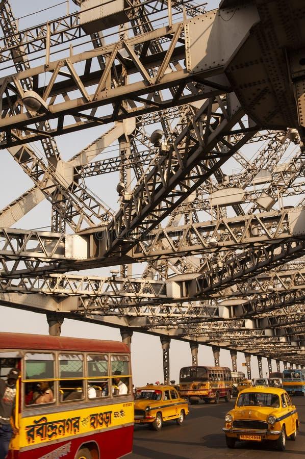 加尔各答/印度 — 2012年2月2日:公共交通通过历史悠久的豪拉桥,穿过呼啸的河 库存照片