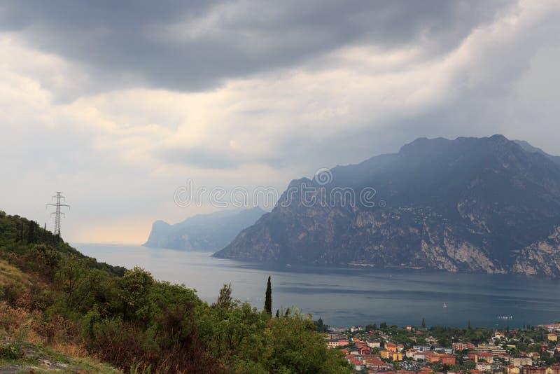 加尔达湖、湖边与黑暗的暴风云,意大利的村庄Torbole和山全景  免版税库存图片