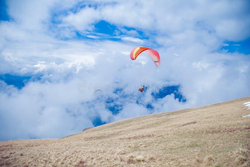 加尔达湖附近云中飞行的两名滑翔伞 免版税图库摄影