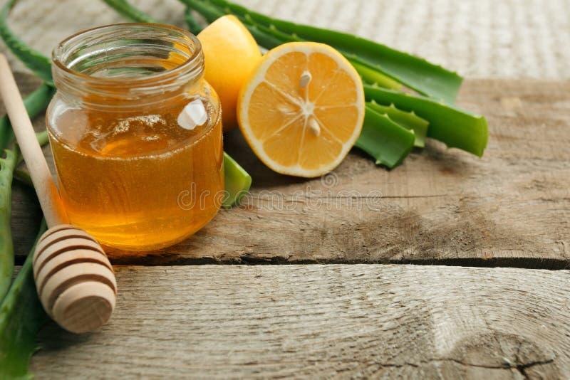 加强的免疫健康成份在木背景-在瓶子、柠檬和芦荟维拉叶子的蜂蜜 库存图片