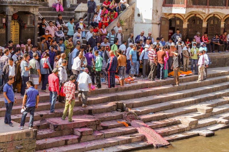 加德满都,尼泊尔- 2016年11月03日:对火葬仪式的准备沿Pashupatinath寺庙的圣洁巴格马蒂河 免版税库存图片