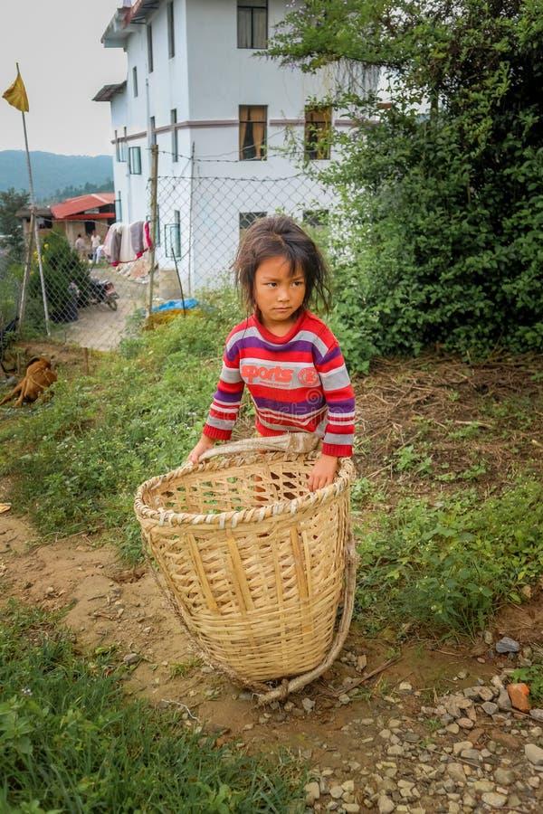 加德满都,尼泊尔- 2016年9月22日:运载一个篮子的未认出的尼泊尔小女孩在她的村庄尼泊尔 免版税库存照片