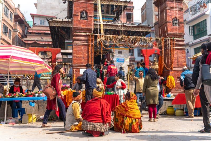 加德满都18 03 2019年:坐整洁的寺庙的叫化子在durbar正方形在加德满都 免版税库存照片