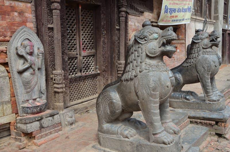 加德满都,尼泊尔, 2013年9月, 27日,尼泊尔场面:石狮子临近古庙 免版税库存照片