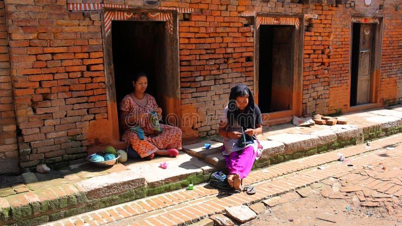 加德满都,尼泊尔- 2013年6月:编织在街道的地方妇女 免版税库存照片