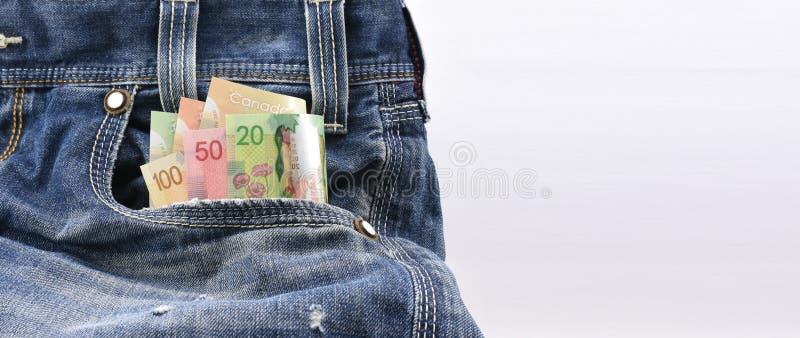加拿大元在蓝色牛仔布牛仔裤的价值20, 50和100装在口袋里,在收入金钱,挽救金钱的概念 免版税库存照片