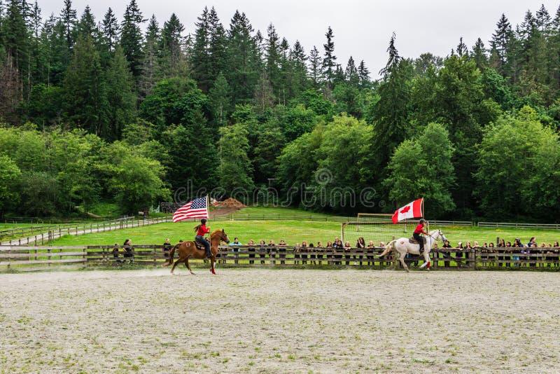 加拿大枫岭 — 2019年7月5日:在最后一天的夏令营秀上,骑马者在赛场上用旗帜 免版税图库摄影