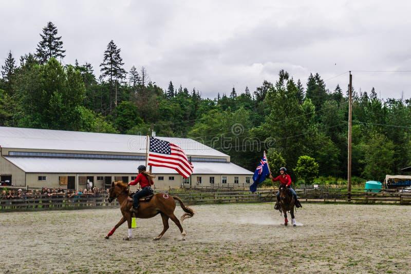 加拿大枫岭 — 2019年7月5日:在最后一天的夏令营秀上,骑马者在赛场上用旗帜 图库摄影