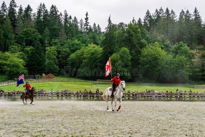 加拿大枫岭 — 2019年7月5日:在最后一天的夏令营秀上,骑马者在赛场上用旗帜 免版税库存照片