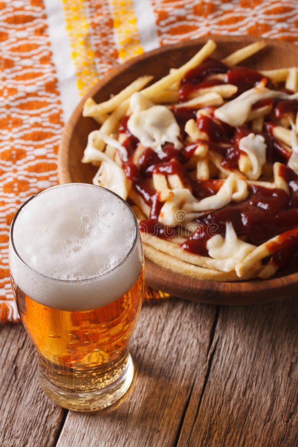 加拿大食物:啤酒和油炸物与调味汁特写镜头 垂直 免版税库存照片
