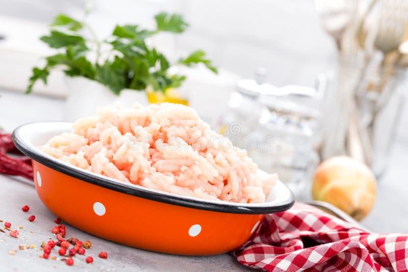 加料碎肉 在碗的未加工的碎鸡肉在白色厨房用桌上 新鲜的剁碎的鸡胸脯肉 免版税库存图片