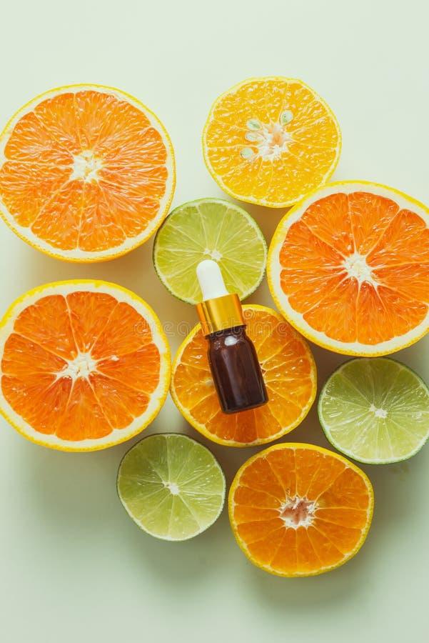 加柠檬、橙、橘和维生素C的棕色瓶 白色背景 免版税图库摄影