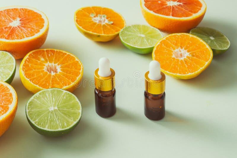加柠檬、橙、橘和维生素C的棕色瓶 白色背景 库存照片