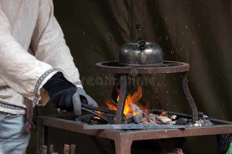 加热在炽热煤炭的铁匠金属,当在上面时的茶罐开水 伪造金属的工匠手,红色火花是 免版税图库摄影